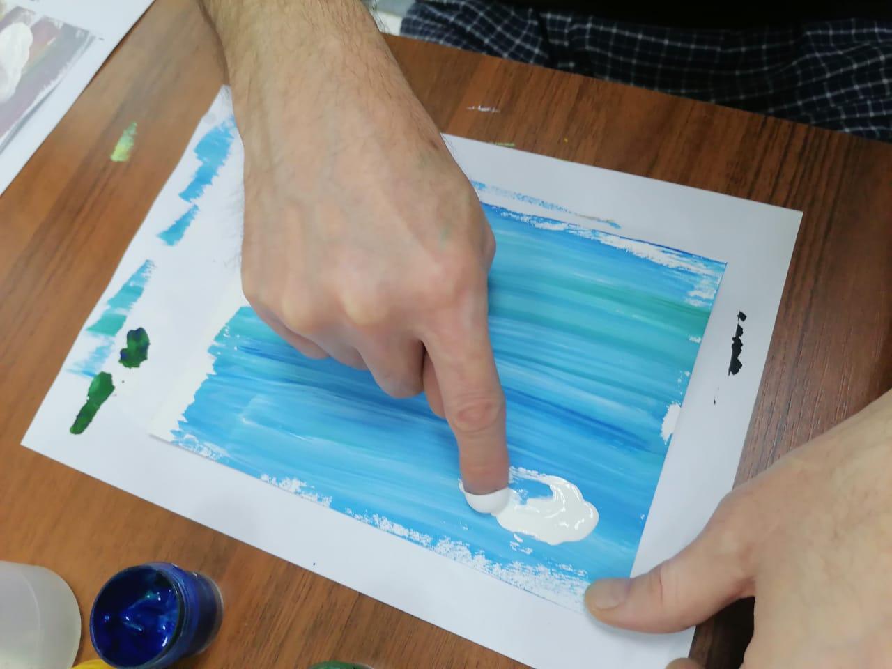 Палец указывает на рисунок, выполненный акварелью