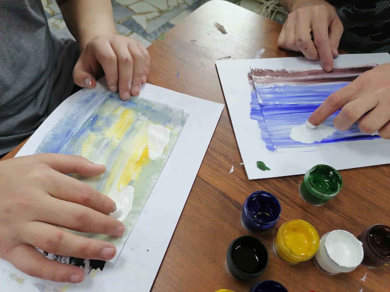 руки трогают акварельные рисунки
